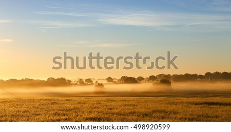 Misty sunrise on farmland. Farm pasture field covered with layers of fog