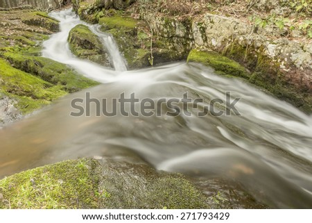 Misty waterfall deep in the woods cascading down the mossy rocks - stock photo