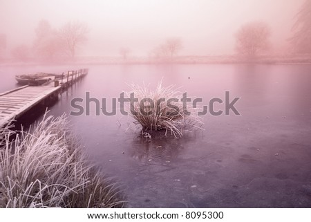 Misty Waters, Sunset over Frozen Lake and Jetty with some light grain to Fog - stock photo