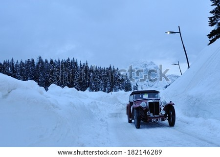 MISURINA, ITALY - FEBRUARY 21: A red MG TB takes part to the WinteRace classic car race on February 21, 2014 in Misurina. This car was built in 1938. Shot with some blue cast of the after sunset hour - stock photo