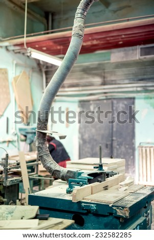 Mitre saw cutting a wooden board at a steel and wood factory. Lathe, drilling and milling tools and objects - stock photo