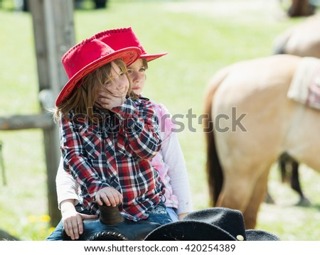 MITROV. CZECH REP - May 7, 2016: Two cute little girl with red hat riding on the ranch. MITROV, 7 MAY 2016, CHECH REPUBLIC