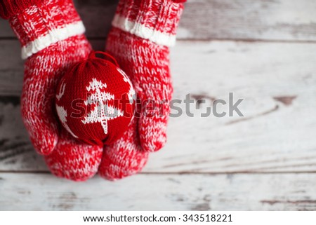 Mitten with christmas ball on wood floor. Winter decoration - stock photo
