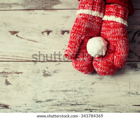 Mitten with snowball on wood floor. Winter decoration - stock photo