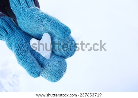 Mittens holding a snow heart shape - stock photo