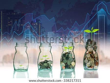 Mix coins and seed in clear bottle on trading graph with cityscape background,Business investment growth concept - stock photo