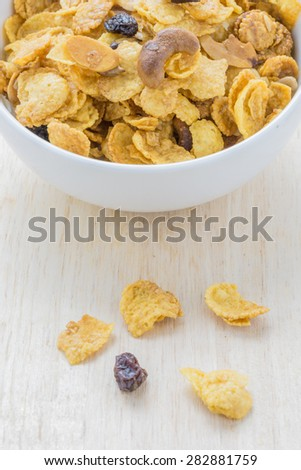 Mix corn flake cereal in a white bowl on the table.