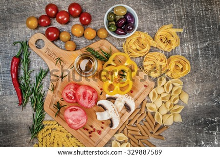 Mix different colored raw whole grain pasta and noodles. Organic pasta of different types of tubes up shells on a wooden table with tomatoes and mushrooms. Photo products on top - stock photo