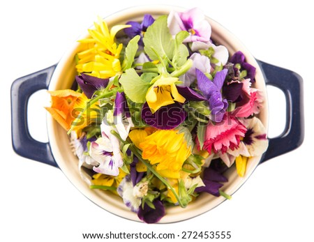 Mix edible flower salad in a blue single pot over white background - stock photo