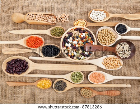 Mix from different beans, legumes, peas, lentils in spoon on the sackcloth background - stock photo