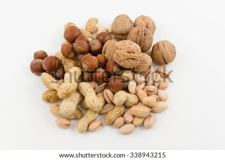 mix from various nuts lies a hill on a white background