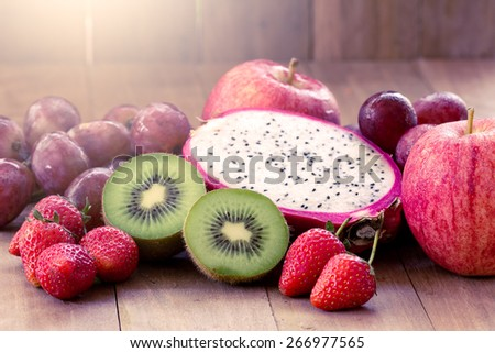Mix fruits on wooden background - stock photo