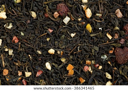 Mix green tea with raspberries, orange peel and candied fruit. - stock photo