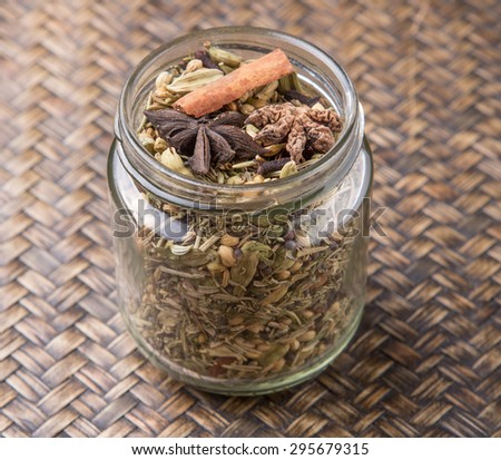 Mix herbs and spices in mason jar over wicker background - stock photo