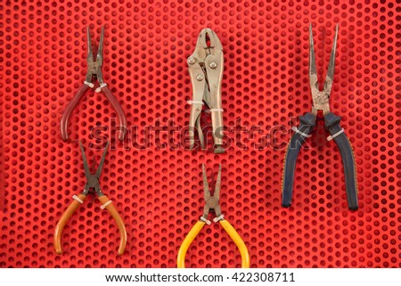 Mix maintenance tools on red wall - stock photo