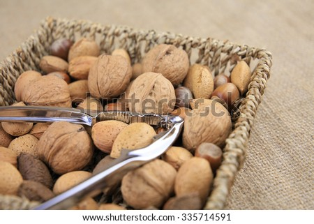 Mix nuts and tongs in a basket, linen background.