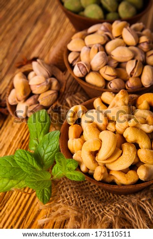 mix nuts - cashew, wasabi and pistachio on wooden table  - stock photo