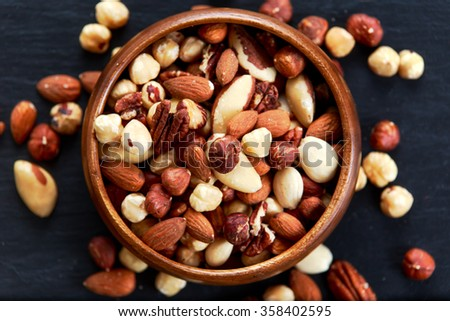 mix nuts in wooden bowls on old blue stone background. - stock photo