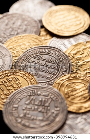 Mix of ancient golden and silver islamic coins, closeup, selective focus, vertical - stock photo