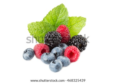 Mix of berries. Raspberries, blueberries and blackberries on a white background with leaves mint. Isolated.