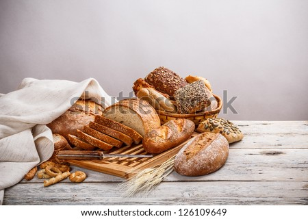 Mix of bread on cutting board and on basket - stock photo