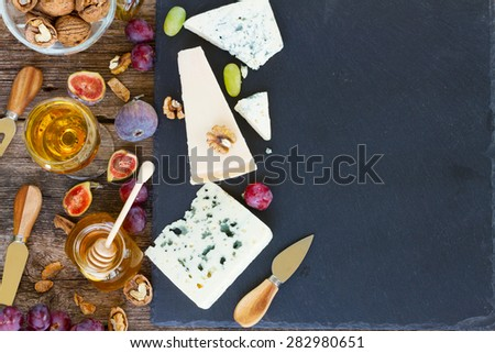 Mix of cheese on black cutting board with honey and wine, top view, copy space on black stone background - stock photo