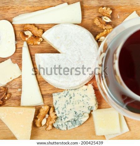 mix of cheeses on wooden plate - stock photo