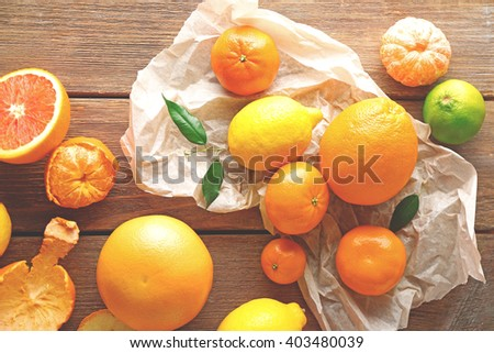 Mix of citrus fruits on wooden table - stock photo