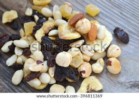 Mix of different nuts and candied fruit on wooden table - stock photo