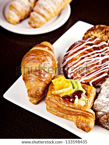 Mix of different pastry on white plate - stock photo