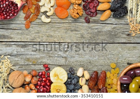 Mix of dried fruits and nuts, barley, wheat, olives, pomegranate on wooden table  - symbols of judaic holiday Tu Bishvat. Copyspace background.Top view. - stock photo