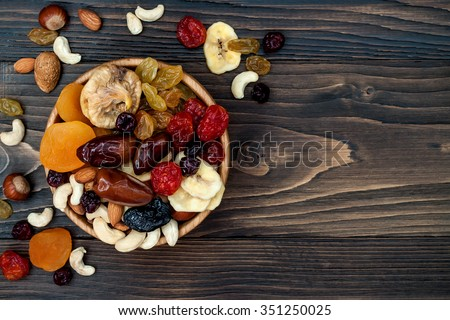 Mix of dried fruits and nuts on a dark wood background with copy space. Top view. Symbols of judaic holiday Tu Bishvat - stock photo