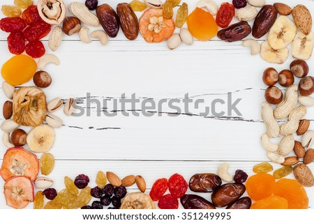 Mix of dried fruits and nuts on a white vintage wood background with copy space. Top view. Symbols of judaic holiday Tu Bishvat