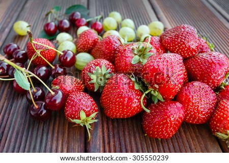 Mix of fresh and juicy berries in the summer garden on wooden texture background - stock photo