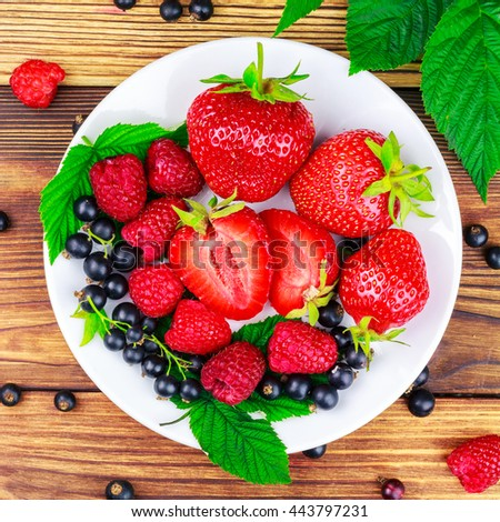 Mix of fresh and ripe berries in plate on wooden background, top view - stock photo