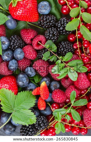 mix  of fresh  berries with green  leaves background - stock photo