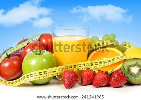 mix of fresh fruit as apple , grapes, strawberries, kiwi and vegetables as tomato with  glass of orange juice all wrapped in measure tape on a blue sky background in healthy nutrition and diet concept - stock photo