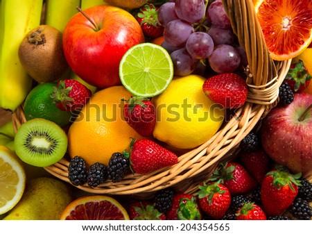 Mix of fresh fruits on wicker basket - stock photo