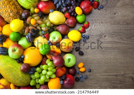 Mix of Fresh Fruits  with water drops on dark wooden table - copy space - stock photo