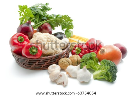 Mix of fresh ripe vegetables arranged in a wicker basket and around isolated on white background - stock photo