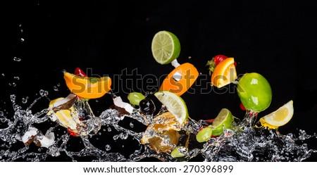 Mix of fruit with water splashes isolated on black background - stock photo