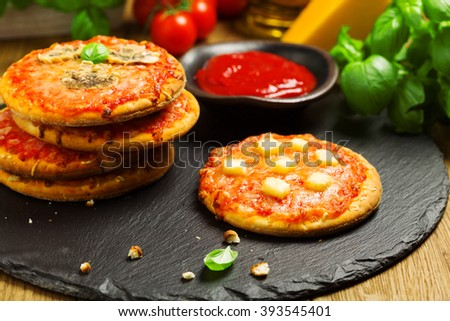 Mix of mini pizzas on a stone try - stock photo