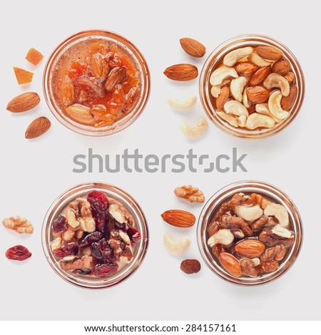 Mix of nuts in glass pots with honey, dried fruits and flower pollen. Ingredients lie separately near desserts. Healthy sweets concept. Top view of collection. - stock photo