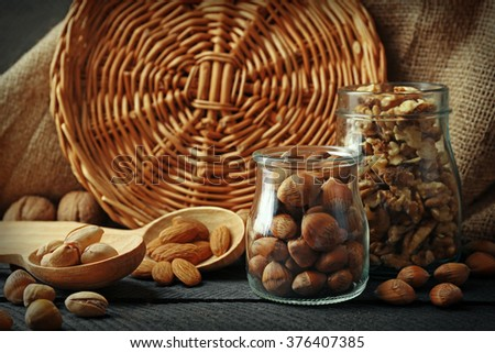 Mix of nuts in the glass jars and wooden spoon, on the table - stock photo