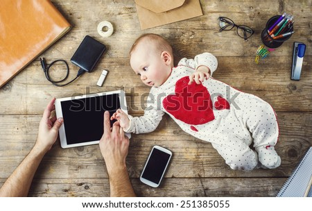 Mix of office supplies and gadgets on a wooden desk background alongside with cute little baby. View from above. - stock photo