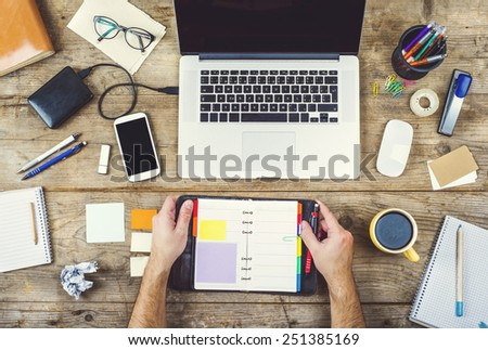 Mix of office supplies and gadgets on a wooden desk background. View from above. - stock photo