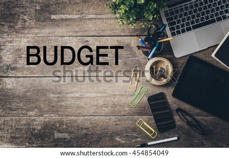 Mix of office supplies and gadgets on a wooden desk with text - Budget - stock photo