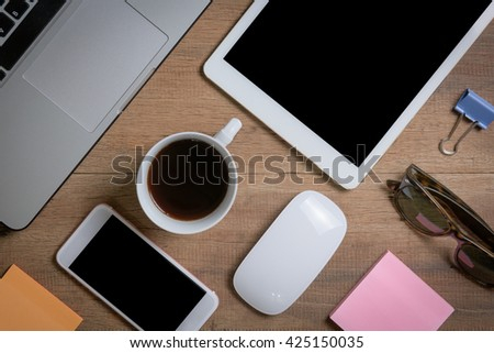 Mix of office supplies and gadgets on a wooden table background. Flat lay