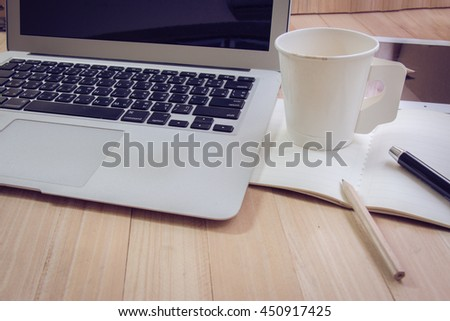 Mix of office supplies,  cup of coffee and laptop in the office put on the wood texture background