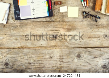 Mix of office supplies on a wooden table background. View from above. - stock photo